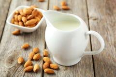 Kruik melk met amandelen op de grijze houten achtergrond Stock Foto