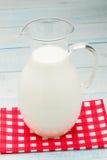 Kruik melk op een rood geruit tafelkleed Royalty-vrije Stock Afbeelding
