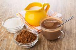 Kruik melk op servet, kommen met cacaopoeder, suiker, cacao met melk, lepel in kop op houten lijst stock afbeeldingen