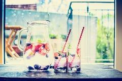 Kruik met bessenlimonade, ijsblokjes en glazen op lijst over terrasachtergrond Royalty-vrije Stock Afbeeldingen