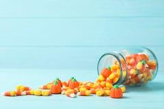 Kruik met heerlijk suikergoed op lijst tegen houten achtergrond stock foto