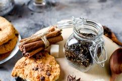 Kruik met thee, eigengemaakte koekjes en kruiden voor thee op donkere bac Stock Fotografie