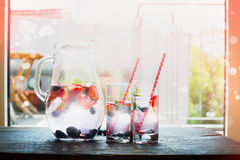 Kruik met water, ijsblokjes en bessen, twee glazen op keukenlijst over de achtergrond van het tuinterras Stock Fotografie