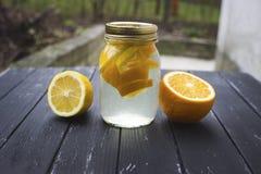 Kruik smakelijke verse limonade met citroen op achtergrond Royalty-vrije Stock Afbeeldingen