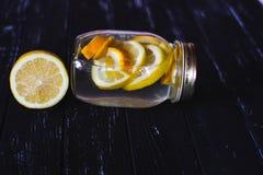 Kruik smakelijke verse limonade met citroen op achtergrond Stock Afbeeldingen