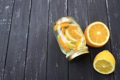 Kruik smakelijke verse limonade met citroen op achtergrond Stock Foto