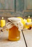 Kruik van honing, pijpjes kaneel en kaarsen Stock Foto's