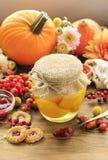 Kruik van ingelegde perziken en mooie de herfstbloemen en installaties Stock Foto