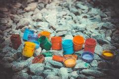 Kruik van onder de verf van verschillende kleuren op de grijze stenen, filter Royalty-vrije Stock Foto's