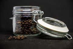 Kruik van peper op zwarte achtergrond stock afbeeldingen