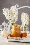 Kruik van van de perzikjam en hyacint bloemen op de achtergrond Stock Afbeeldingen
