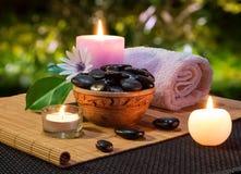 Kruik van zwarte stenen en kaarsen op bamboemat Stock Fotografie