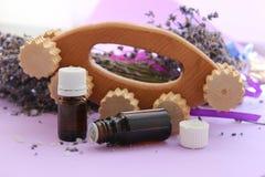 Kruiken etherische oliën en een houten te bestrijden massager cellulite stock fotografie