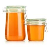 Kruiken honing die op wit wordt geïsoleerdi Stock Fotografie