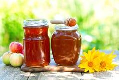 Kruiken honing op houten lijst Stock Fotografie