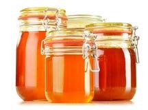 Kruiken honing op wit Royalty-vrije Stock Afbeeldingen
