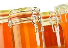 Kruiken honing op wit wordt geïsoleerd dat Stock Foto's