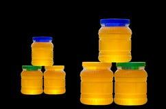 Kruiken honing op zwarte achtergrond wordt geïsoleerd die Royalty-vrije Stock Afbeeldingen