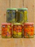 Kruiken met diverse groenten in het zuur Ingeblikte komkommers en tomaten Stock Afbeelding