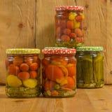 Kruiken met diverse groenten in het zuur Ingeblikte komkommers en tomaten Royalty-vrije Stock Foto's