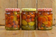 Kruiken met diverse groenten in het zuur Ingeblikte komkommers en tomaten Royalty-vrije Stock Foto