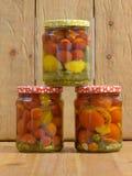 Kruiken met diverse groenten in het zuur Ingeblikte komkommers en tomaten Royalty-vrije Stock Afbeeldingen