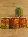 Kruiken met diverse groenten in het zuur Ingeblikte komkommers en tomaten Stock Fotografie