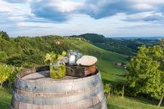 Kruiken met druiven en kaars op houten vat dichtbij wijngaard op zo royalty-vrije stock foto