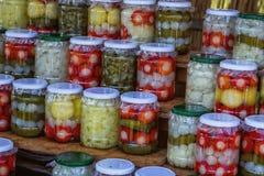 Kruiken met groenten in het zuur, cayennepeper, uien, komkommer en Spaanse pepers royalty-vrije stock foto's