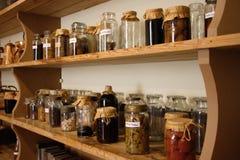 Kruiken met kruiden en andere conserve op een plank royalty-vrije stock foto