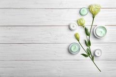 Kruiken met lichaamscrème en bloemen stock afbeeldingen