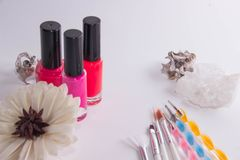 Kruiken met vernisvernissen met leeswijzers voor manicure op een witte achtergrond stock afbeelding