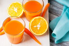 Kruiken met wortelsap, wortel en gesneden sinaasappel Stock Fotografie