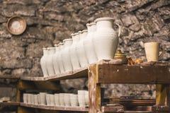Kruiken ongebakken klei op de plank in de aardewerkworkshop Stock Foto's
