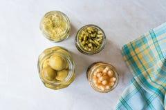 Kruiken van Groenten in het zuur Groene en Witte Asperge, Artisjokhart en Onrijpe Groene Amandelgroenten in het zuur in Glasfles stock fotografie