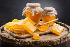 Kruiken van honing en honingraten Stock Afbeeldingen
