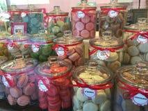 Kruiken van kleurrijke makaroncakes op vertoning in opslagvoorzijde Royalty-vrije Stock Afbeelding