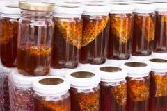 Kruiken verse honing op planken Stock Afbeelding