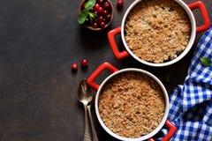Kruimeltaart met Amerikaanse veenbessen en andere bessen, noten op de keukenlijst Mening van hierboven stock foto's