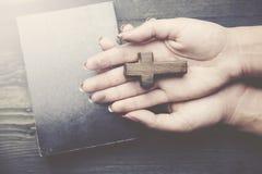 Kruis, boek en vrouwenhand Royalty-vrije Stock Foto's