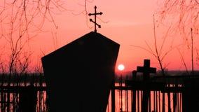 Kruis in de begraafplaats bij zonsondergang gloeiende zon stock footage