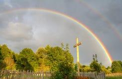 Kruis en regenboog na regen Royalty-vrije Stock Foto's