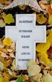 Kruis met Duitse teksten bij het graf in de herfst Stock Afbeelding