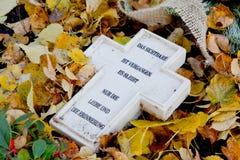 Kruis met Duitse teksten bij het graf in de herfst Stock Foto