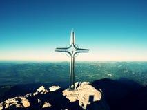 Kruis met halfedeldiesteen bij bergtop wordt opgeheven in Alpen Scherpe piek Royalty-vrije Stock Fotografie