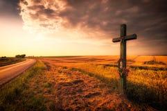 Kruis over het gebied tijdens zonsondergang Royalty-vrije Stock Foto's