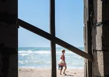 Kruis van raad in het venster die het overzees, het strand overzien en stock foto's