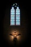 Kruisbeeld in kerk onder gebrandschilderd glasvenster. Royalty-vrije Stock Foto