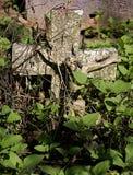 Kruisbeeld van verlaten graf onder onkruid stock foto