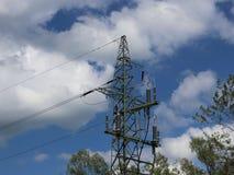 Kruisen de hoogspannings elektrische lijnen de heuvelige mestnost Elektrische post in de zomer onder de open hemel Getelegrafeerd stock foto